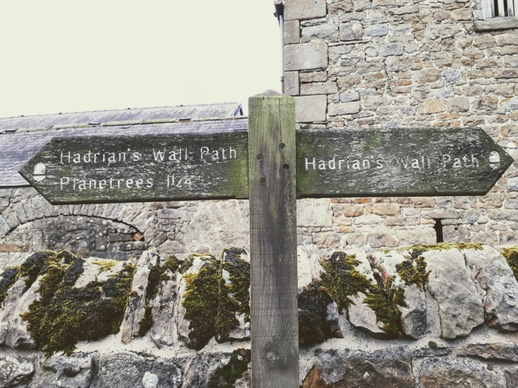 "alt=""hadrians wall path signpost at St Oswald's Farm"""