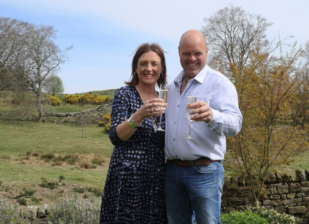 "alt=""Lorraine and John celebrating award with a glass of champagne in the garden, part of five star offer"""
