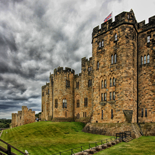 "alt=""rainy days out Alnwick castle exterior with dark skies"""